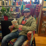 """Peter Rowland reading a copy of his book """"Australia's Birdwatching Megaspots"""" at Blarney Books in Port Fairy"""