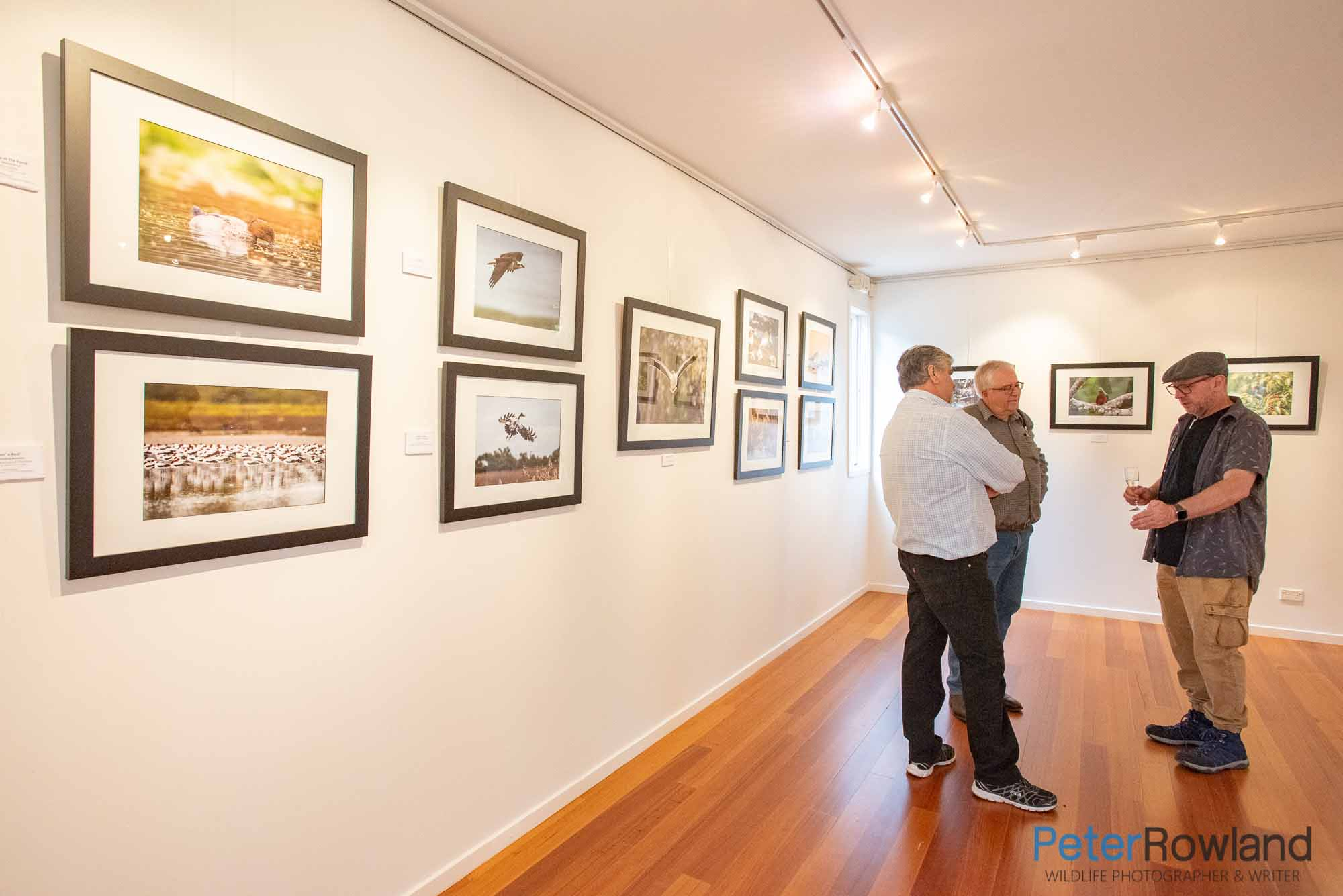 Peter Rowland talking to two men at photographic exhibition